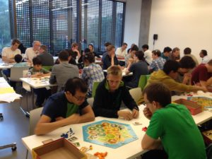 On the closest gameboard on bottom left starting from left to right: Demis Hassabis (gold), Martin Hobemagi (junior gold), James Heppell (silver)